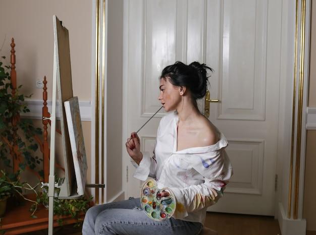 Een jong kunstenaarsmeisje zit bij het raam, houdt een kwast in haar mond en onderzoekt het schilderij zorgvuldig.