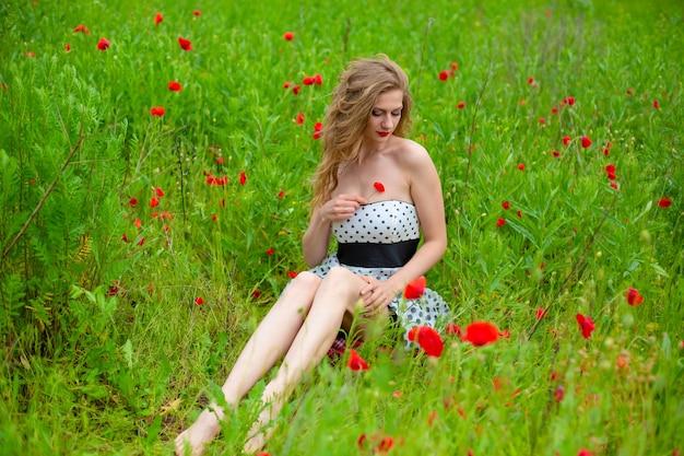 Een jong langharig meisje geniet van de kleuren van de natuur op een bloeiende papaverveld op een hete zomerdag.