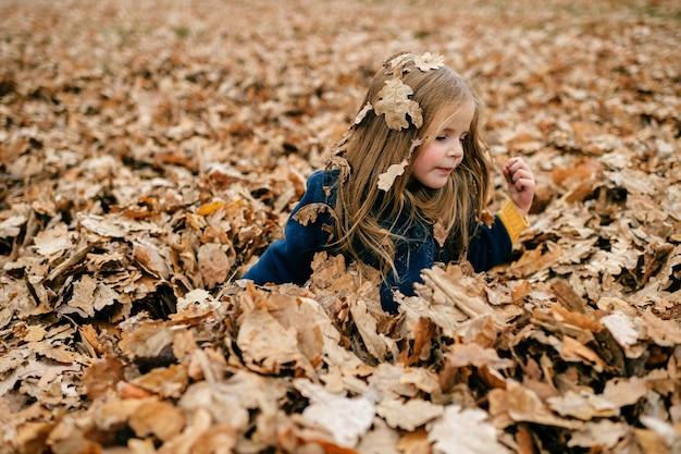 Een jong leuk meisje dat in bladeren speelt
