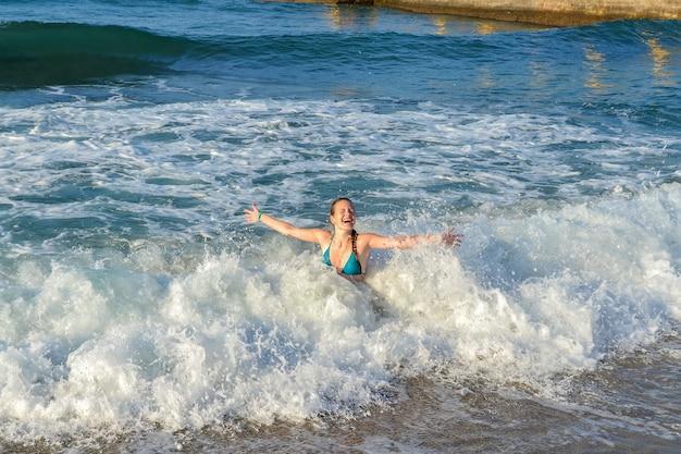 Een jong meisje baadt in de golven van de zee