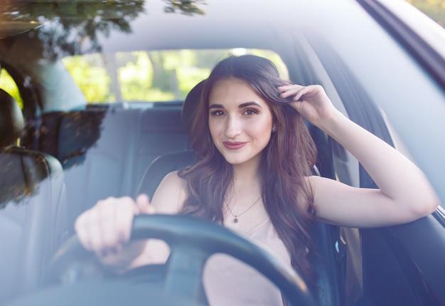 Een jong meisje bestuurt een auto.