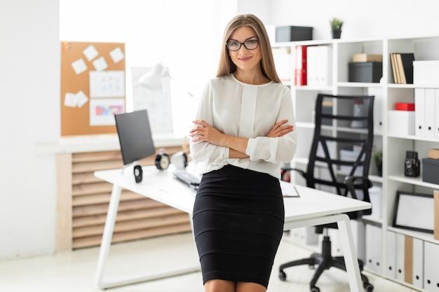 Een jong meisje bevindt zich leunend op een lijst in het bureau.