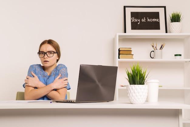Een jong meisje bevriest in het kantoor waar de verwarming is afgesneden als gevolg van een ongeval op de verwarmingsleiding