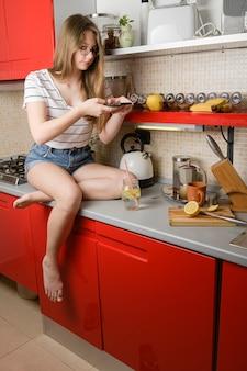 Een jong meisje blogger maakt een foto van haar drankje om het op de keukentafel te laten zien op sociale media