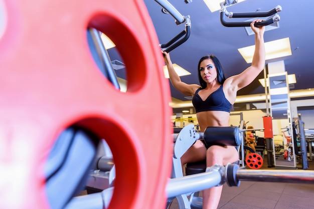 Een jong meisje dat bij een gewichtheffenmachine in de gymnastiek uitwerkt