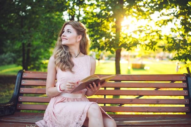Een jong meisje dat een boekzitting op een bank leest bij zonsondergang.
