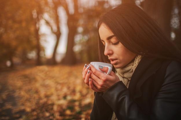 Een jong meisje dat een kop van hete drank houdt en bij de achtergrond van een de herfstbos glimlacht