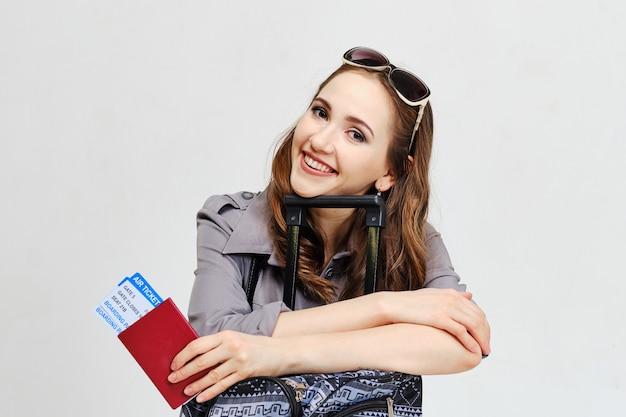 Een jong meisje dat een vliegtuigticket met een paspoort houdt dat op bagage leunt.