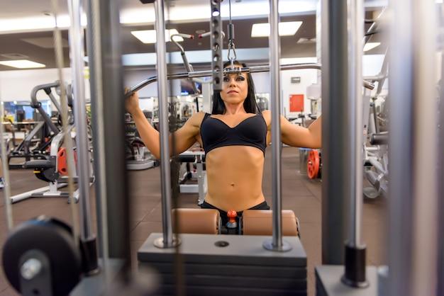 Een jong meisje dat gewichtheffen in de gymnastiek uitvoert