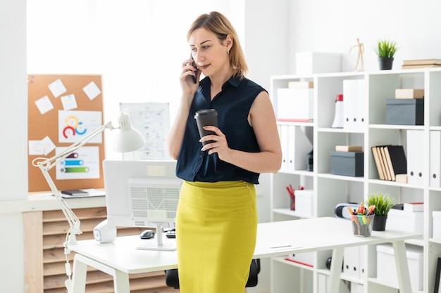 Een jong meisje dat op de telefoon in het bureau spreekt en een glas koffie houdt.