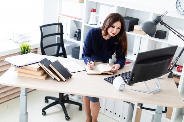 Een jong meisje dat zich dichtbij de lijst bevindt en met een computer en een dagboek werkt.