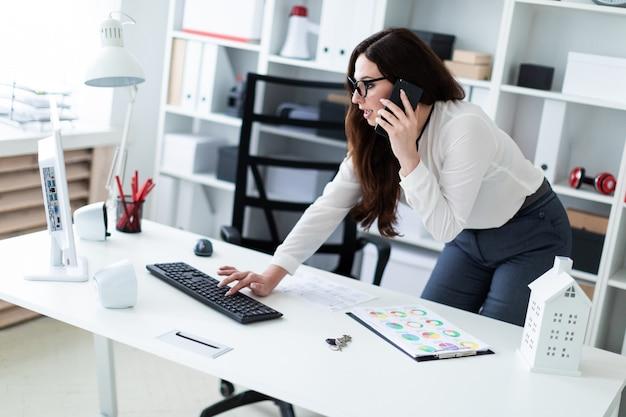 Een jong meisje dat zich dichtbij de lijst bevindt, op het toetsenbord typt en op de telefoon spreekt.