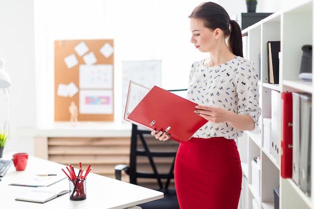 Een jong meisje dat zich in het kantoor bevindt en een rode map met documenten vasthoudt.