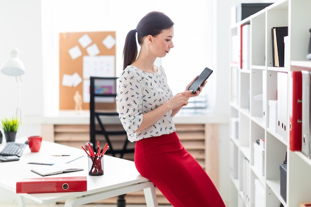 Een jong meisje dat zich in het kantoor bevindt en een telefoon houdt.