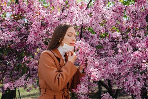 Een jong meisje doet haar masker af en ademt diep na het einde van de pandemie op een zonnige lentedag, voor bloeiende tuinen. beschermings- en preventiecovid 19.