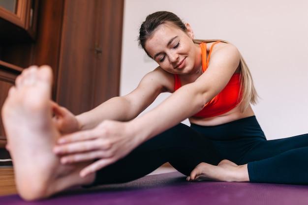 Een jong meisje doet yoga in een lichte kamer