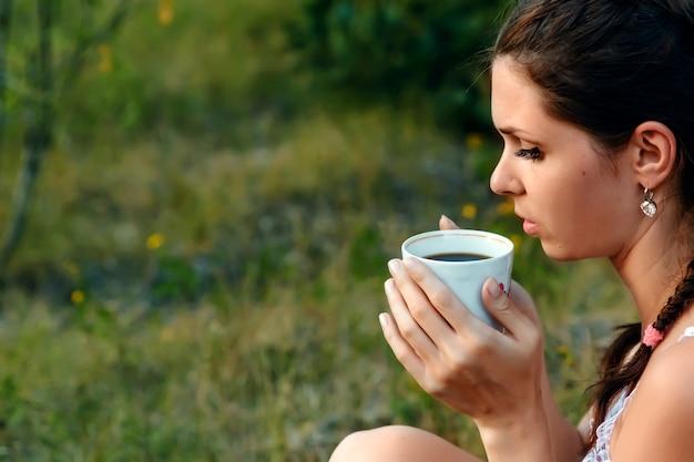 Een jong meisje drinkt koffie en kijkt in de verte naar de zonsondergang, wachtend op iemand. de verwachting, het verlangen, de fantasie, de dromen. copyspace.