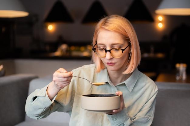 Een jong meisje eet soep in een café en houdt een bord in haar handen