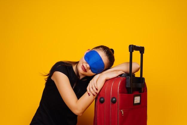 Een jong meisje gaat op reis, slapend op een grote rode koffer, voor een masker om te slapen