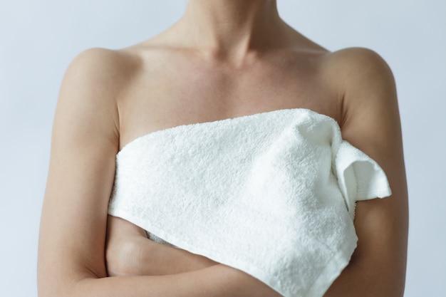 Een jong meisje gebruikt een handdoek om naaktheid te verdoezelen.
