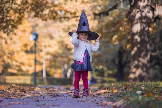 Een jong meisje gekleed in het zwart als een heks met hoed