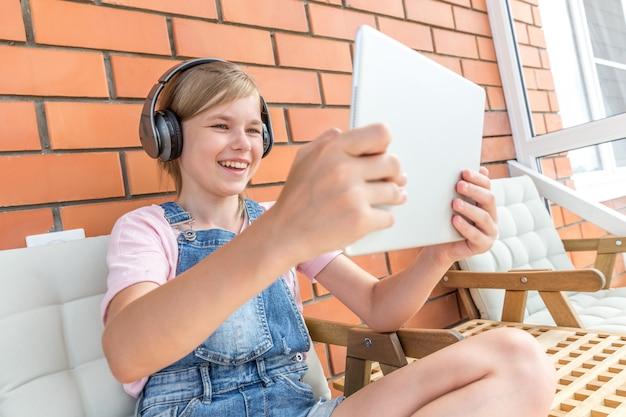 Een jong meisje geniet van het luisteren naar muziek op haar koptelefoon met tablet