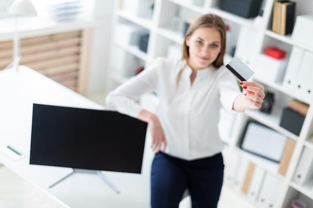 Een jong meisje ging op de tafel zitten en hield een bankkaart vast