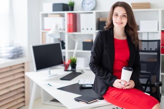 Een jong meisje ging op een tafel in het kantoor zitten en hield een glas koffie vast.