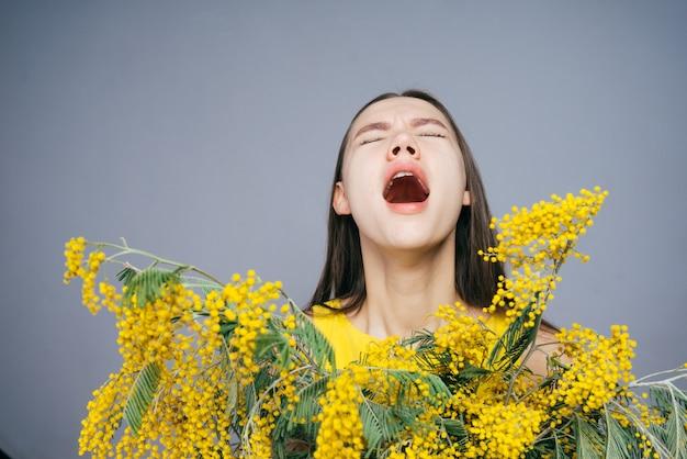 Een jong meisje houdt een groot boeket gele mimosa vast, niest omdat ze allergisch is voor bloemen