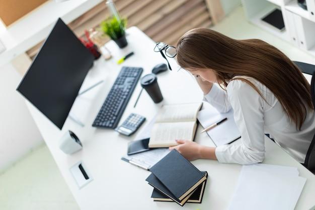 Een jong meisje houdt van een bril en werkt op kantoor met boeken en documenten.