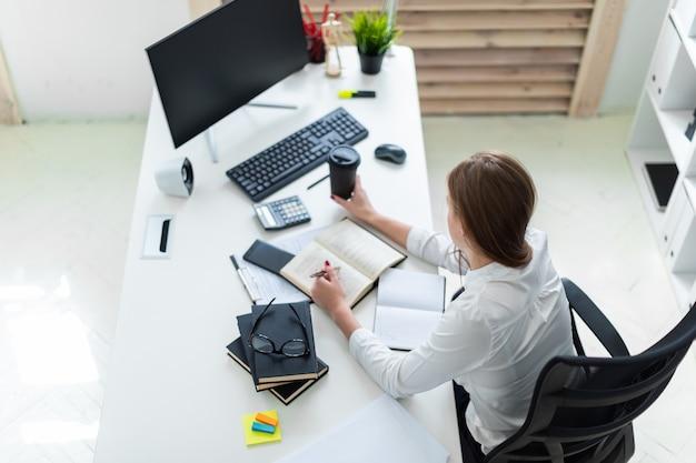 Een jong meisje houdt van een glas koffie en werkt op kantoor met boeken, computer en documenten.