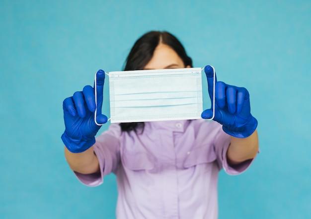 Een jong meisje in blauwe handschoenen houdt een medisch masker voor zich. de arts of verpleegkundige bereidt zich voor op het werk.