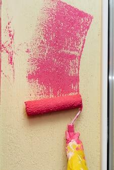 Een jong meisje in close-up schildert een gele muur in roze