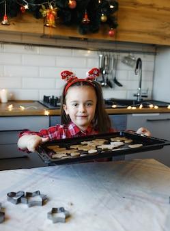 Een jong meisje in de keuken heeft een dienblad met koekjes in haar handen