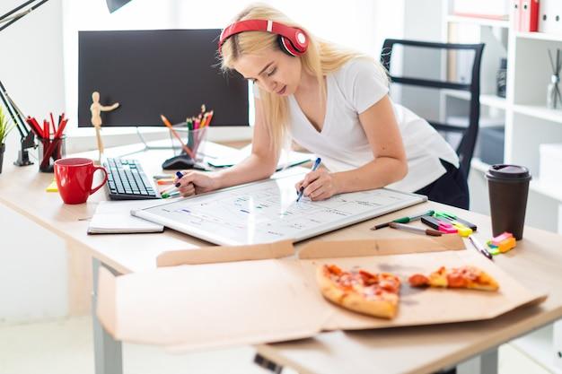 Een jong meisje in de koptelefoon staat bij de tafel en houdt een marker in haar hand. op de tafel ligt een magnetisch bord.
