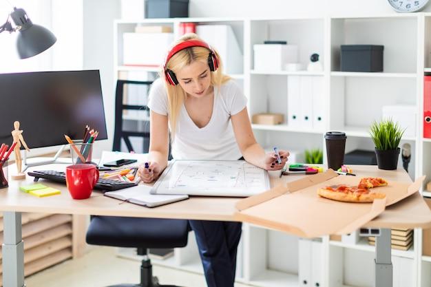 Een jong meisje in de koptelefoon staat bij de tafel en houdt een marker in haar hand.
