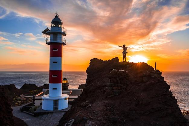 Een jong meisje in de zonsondergang bij de punta de teno-vuurtoren op het eiland tenerife, canarische eilanden