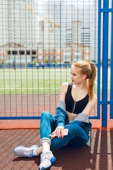 Een jong meisje in een blauw sportpak met een zwarte top zit bij een hek op het stadion. ze luistert naar de muziek met een koptelefoon. ze heeft een aantrekkelijk figuur.