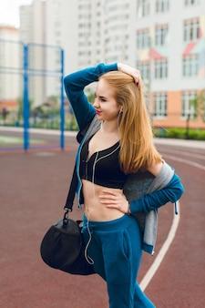 Een jong meisje in een blauw trainingspak met een kort t-shirt gaat het stadion in. ze draagt een tas. ze heeft lang haar en een goed figuur.