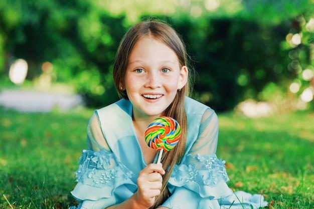 Een jong meisje in een blauwe jurk ligt op het gras in het park met een zoete lolly