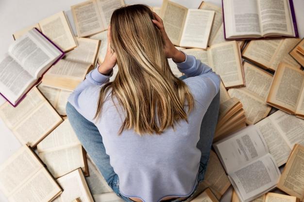 Een jong meisje in een blauwe trui en spijkerbroek zit op een stapel open boeken met haar hoofd in haar handen. achteraanzicht. onderwijs en kennis.