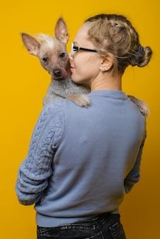 Een jong meisje in een bril en een trui knuffelt haar chinese crested dog op een gele achtergrond