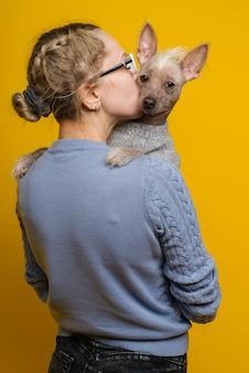 Een jong meisje in een bril en een trui kust haar chinese crested dog op een gele achtergrond