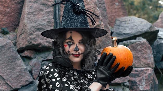 Een jong meisje in een carnavalskostuum met een pompoen
