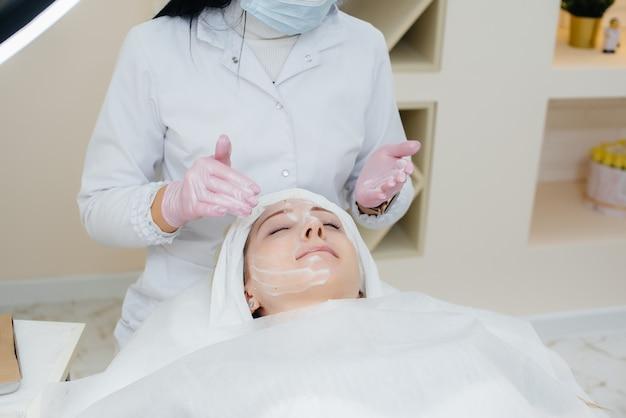 Een jong meisje in een cosmetologie-kantoor ondergaat procedures voor de verjonging van de gezichtshuid. cosmetologie.