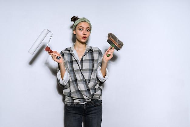 Een jong meisje in een geruit hemd die reparaties aan het doen is in haar nieuwe appartement, met een roller en een schilderij voor aan de muur