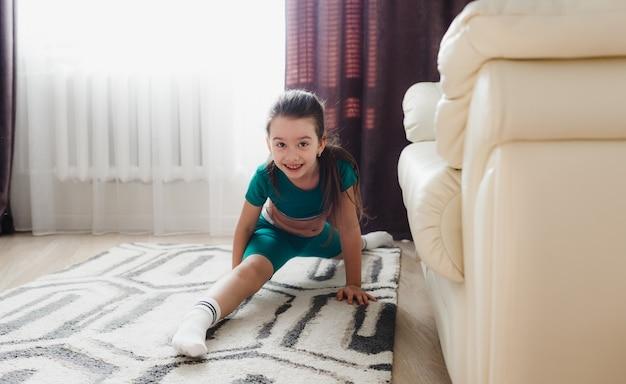 Een jong meisje in een groen trainingspak doet thuis sportoefeningen