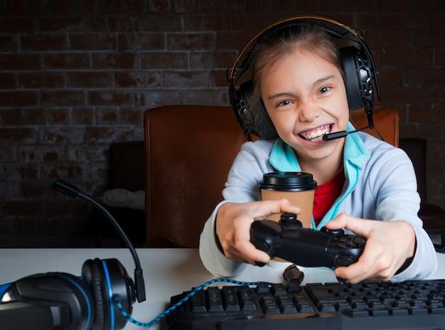 Een jong meisje in een grote koptelefoon met microfoon zit voor een monitor en speelt videogames met een blij opgewonden gezicht. winnen.