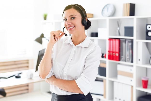 Een jong meisje in een koptelefoon met een microfoon bevindt zich in een helder kantoor.