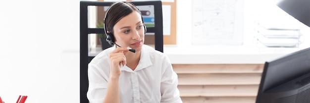 Een jong meisje in een koptelefoon met een microfoon zit aan een computer tafel.